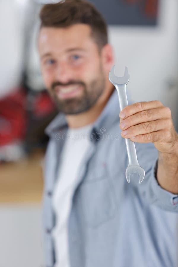 Chave inglesa masculina de sorriso da exibição do mecânico do retrato imagem de stock royalty free