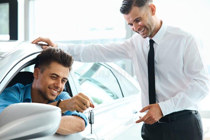 Chave nova cedendo do carro do vendedor de carro ao cliente na sala de exposições imagens de stock
