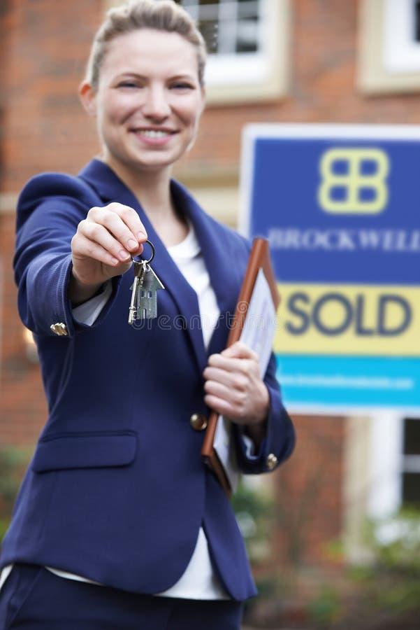 Chave residencial da terra arrendada de propriedade da parte externa ereta fêmea do corretor de imóveis imagem de stock