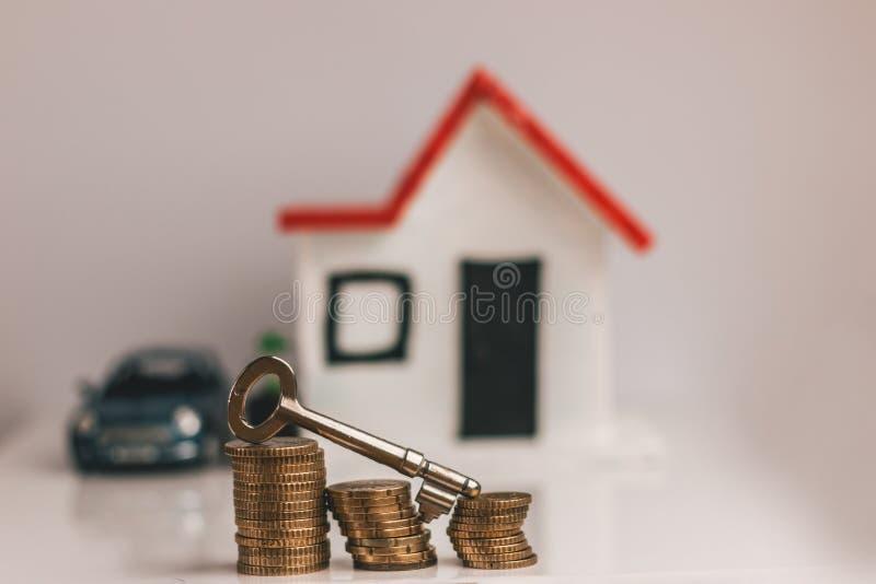 Chave sobre uma pilha de moedas com uma casa e um carro borrados no fundo: bens imobiliários, propriedade, hipoteca, conceito fotografia de stock