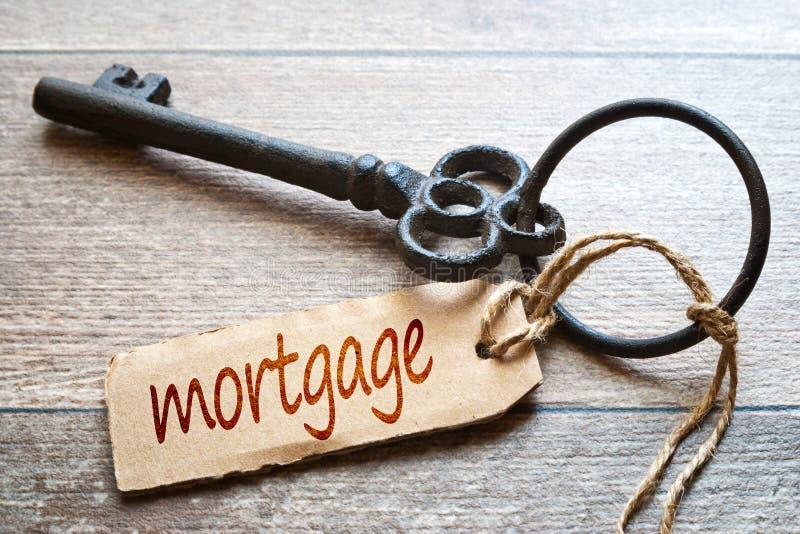 Chave velha chave velha com etiqueta de papel - texto da hipoteca - no fundo de madeira com etiqueta de papel - texto da hipoteca foto de stock royalty free