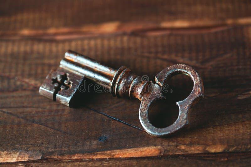 Chave velha do metal em um fundo de madeira imagem de stock royalty free