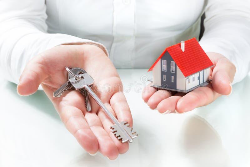 Chaves cedendo do mediador imobiliário à casa fotos de stock royalty free