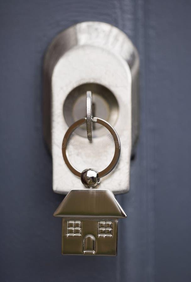Chaves da casa em uma porta cinzenta fotografia de stock royalty free