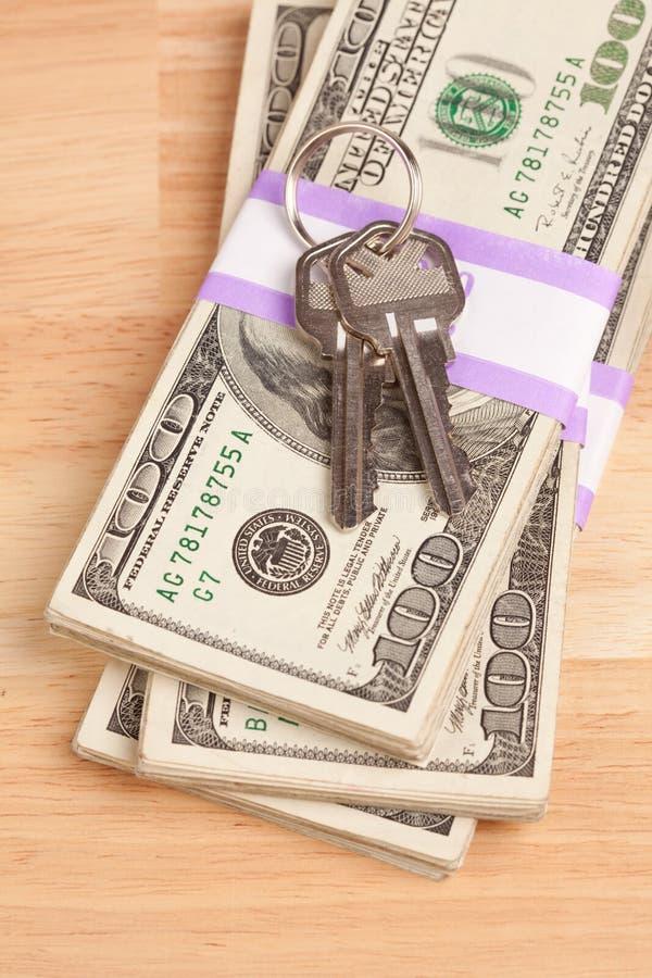 Chaves da casa na pilha de dinheiro imagens de stock