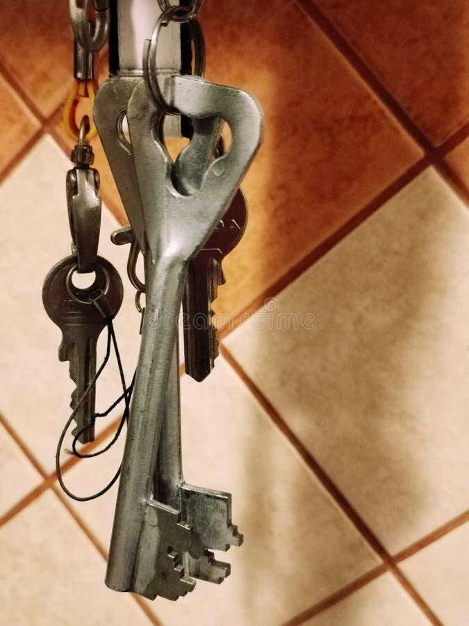 Chaves de suspens?o do metal velho em um fundo de telhas alaranjadas da cozinha fotos de stock royalty free