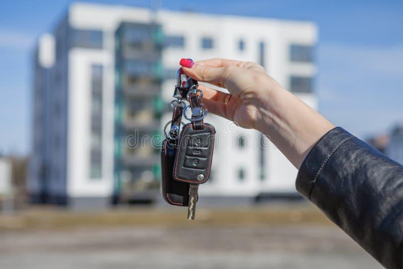Chaves do carro na mão de uma menina em um fundo borrado de uma casa nova fotografia de stock royalty free