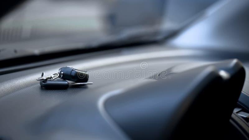 Chaves do carro no fim do painel acima, motorista que sae da auto aberta estacionada, roubo de carro fotos de stock