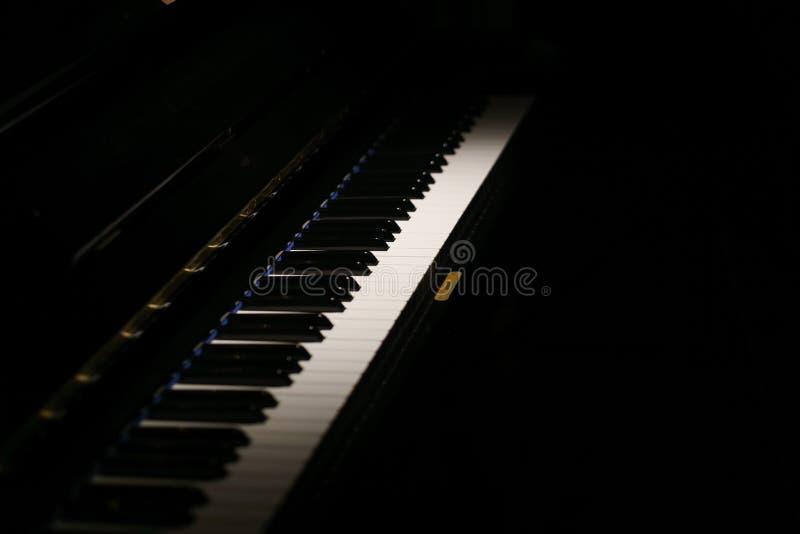 Chaves do piano de um piano clássico na obscuridade imagem de stock royalty free