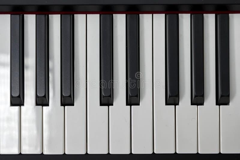 Chaves simples e limpas do piano, uma oitava, close up da música, espaço para o texto no fundo preto fotos de stock royalty free