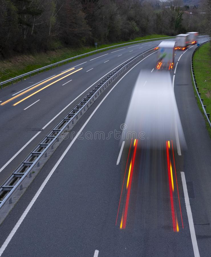 Che accelera il mosso i camion con l'ardore si accende sulla strada principale immagine stock libera da diritti