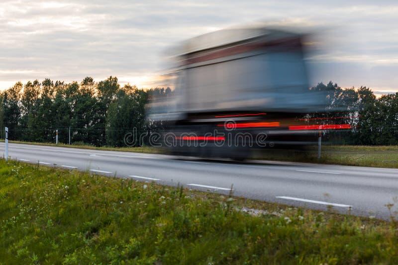 Che accelera il mosso i camion imminenti con l'ardore si accende sul fotografia stock libera da diritti
