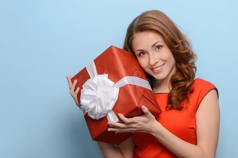Che cosa è dentro questa scatola? Giovane donna attraente che tiene un regalo b fotografia stock libera da diritti