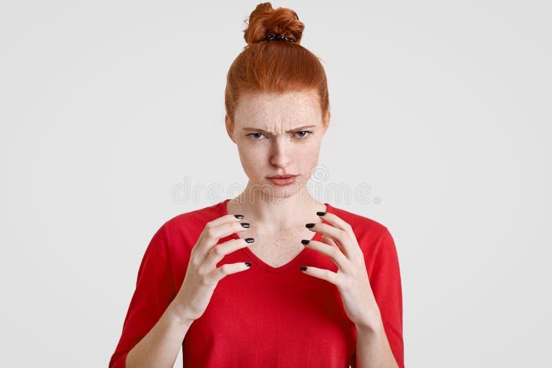 Che cosa! La donna freckled infastidita scontrosa tiene le mani nella parte anteriore, guarda con rabbia, prova a controllare le  immagini stock