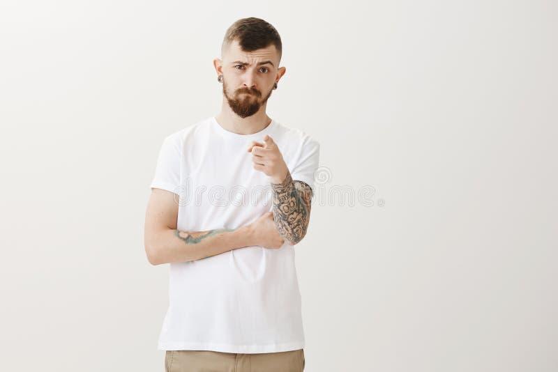 Che cosa sono voi che esaminate Ritratto dell'uomo bello deludente rigoroso con la barba ed i tatuaggi, indicante alla macchina f fotografia stock libera da diritti