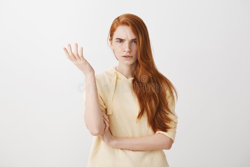 Che cosa sono voi che parlate, assurdità Colpo dello studio della femmina frustrata con capelli rossi che gesturing con la palma  fotografia stock