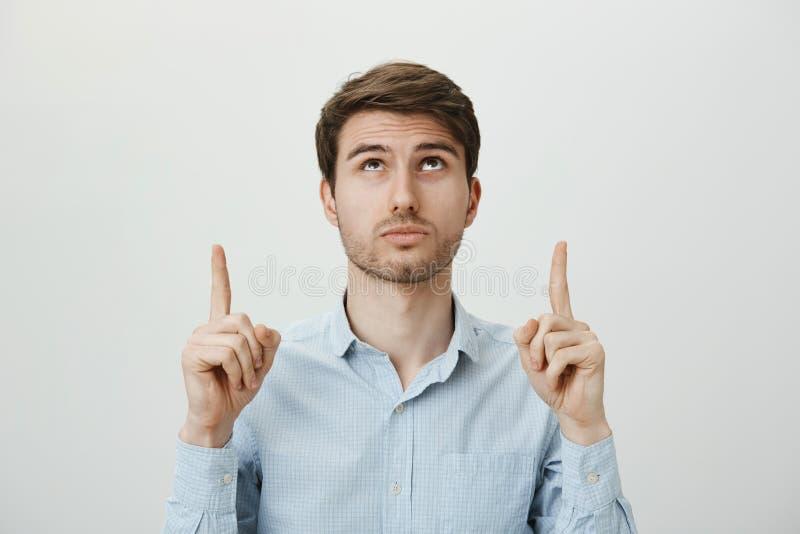 Che cosa sta accadendo di sopra Lo studio ha sparato bello del maschio non rasato bianco curioso ed interessato in camicia blu immagini stock libere da diritti