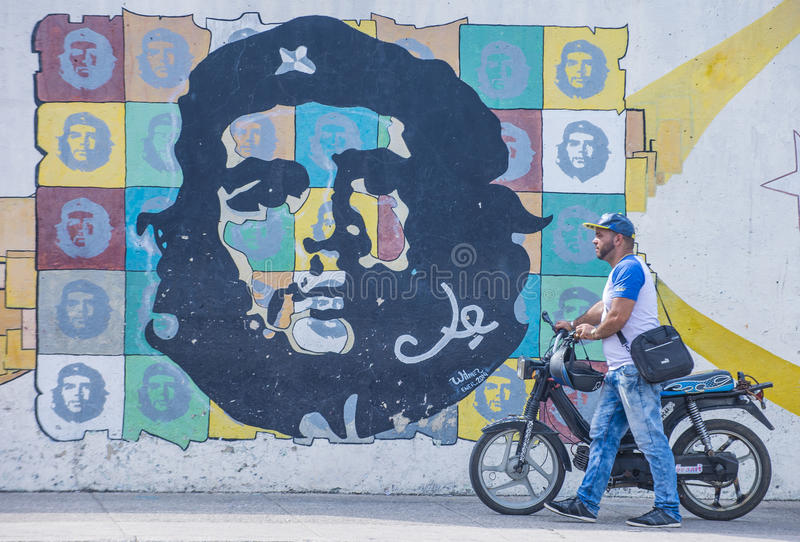 Che Guevara mural. HAVANA, CUBA - JULY 18 : A man with a motorcycle walking past a mural of Che Guevara in old Havana street on July 18 2016. The historic center stock images