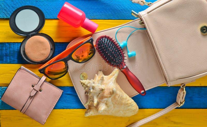 Che ` s nella borsa del ` s delle donne? Accessori della spiaggia di estate, coperture Una borsa, borsa di cuoio, cuffie, specchi fotografie stock libere da diritti