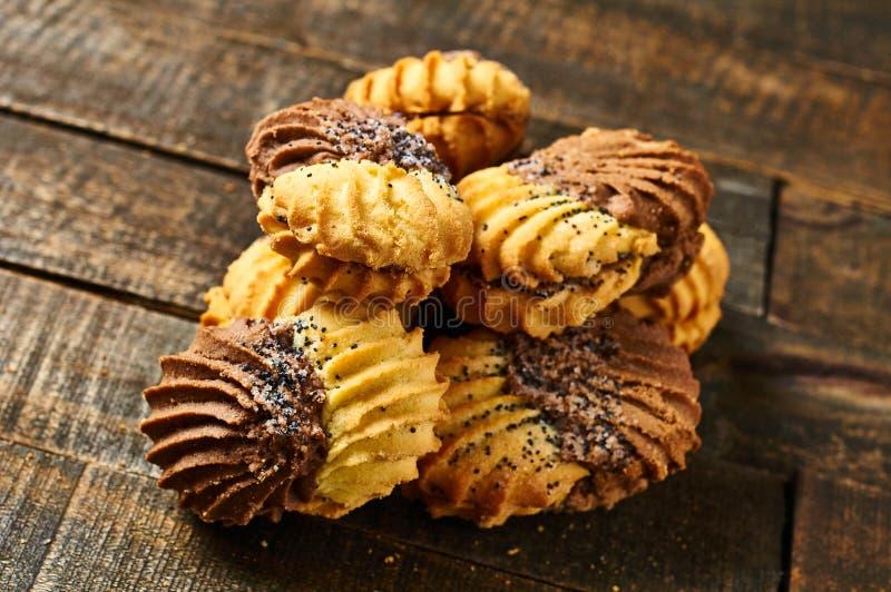 Cheap de biscuits double couleur avec crème et pavot sur table rustique images libres de droits