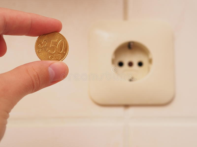 Cheap energy. Hand holding a 50 euro cent coin infront of an outlet - for concepts like cheap energy, savings potential at home or household spendings - focus is stock photo