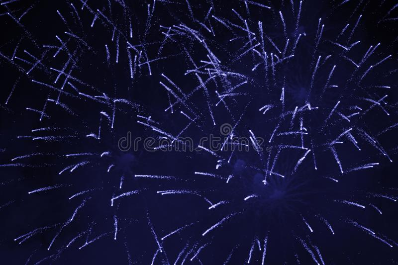 Cheap sparkling fireworks, with a haze, white-blue, against the night sky stock image