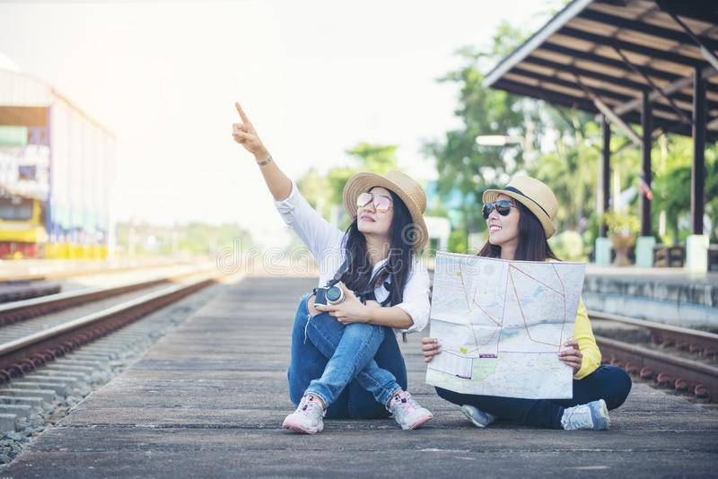 Cheap Travel and Lifestyle concept.Holiday Time,Young Traveler women wearing sneaker and sitting at train station.Asian Backpacker royalty free stock image