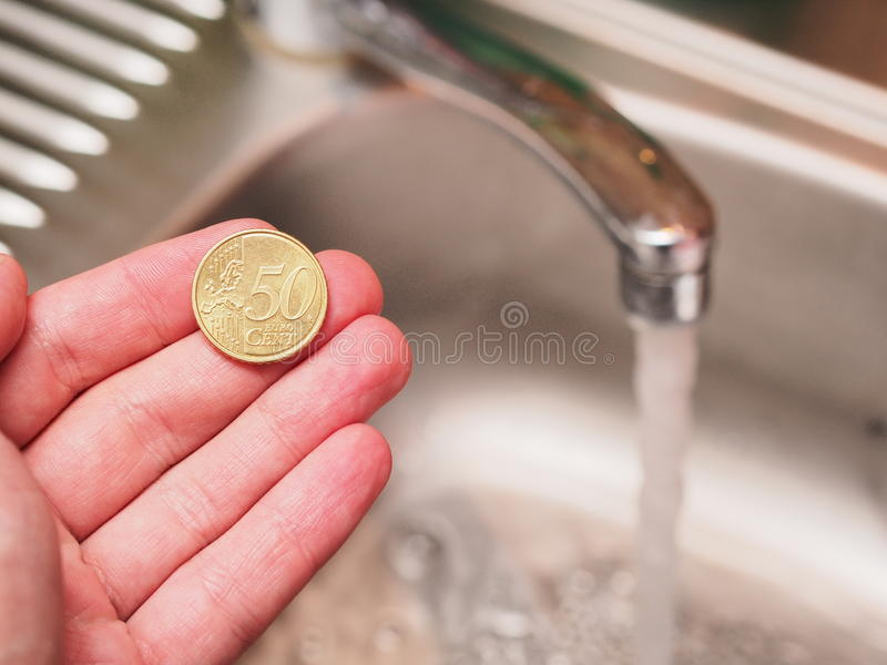 Cheap water. Hand holding a 50 euro cent coin infront of a running faucet - for concepts like cheap water, savings potential at home, household spendings or royalty free stock image