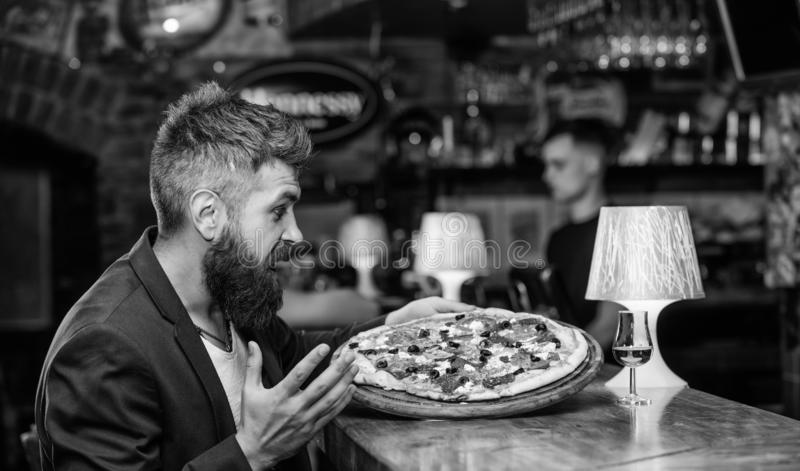 Cheat meal concept. Hipster hungry eat italian pizza. Pizza favorite restaurant food. Fresh hot pizza for dinner. Hipster client sit at bar counter. Man royalty free stock photos