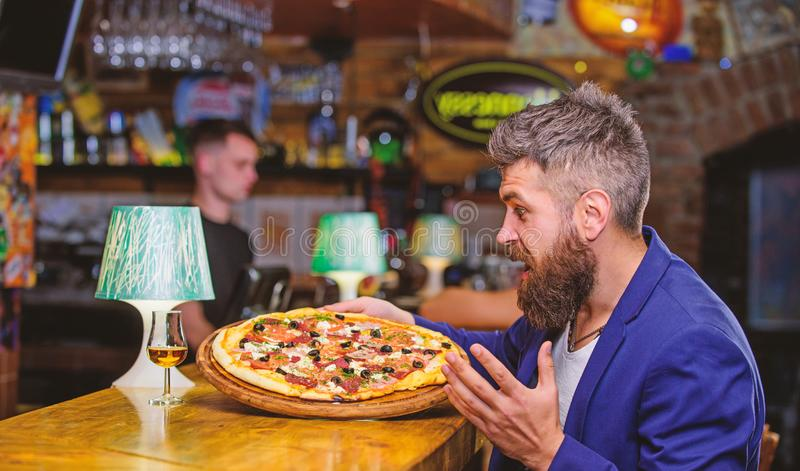 Cheat meal concept. Hipster hungry eat italian pizza. Pizza favorite restaurant food. Fresh hot pizza for dinner. Hipster client sit at bar counter. Man royalty free stock photo