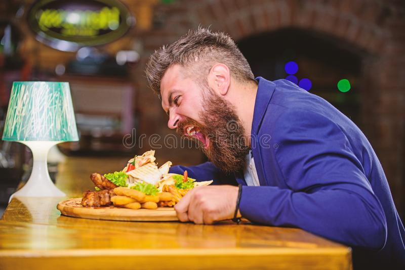 Cheat meal concept. Hipster hungry eat pub fried food. Manager formal suit sit at bar counter. Delicious meal. Man. Received meal with fried potato fish sticks royalty free stock images