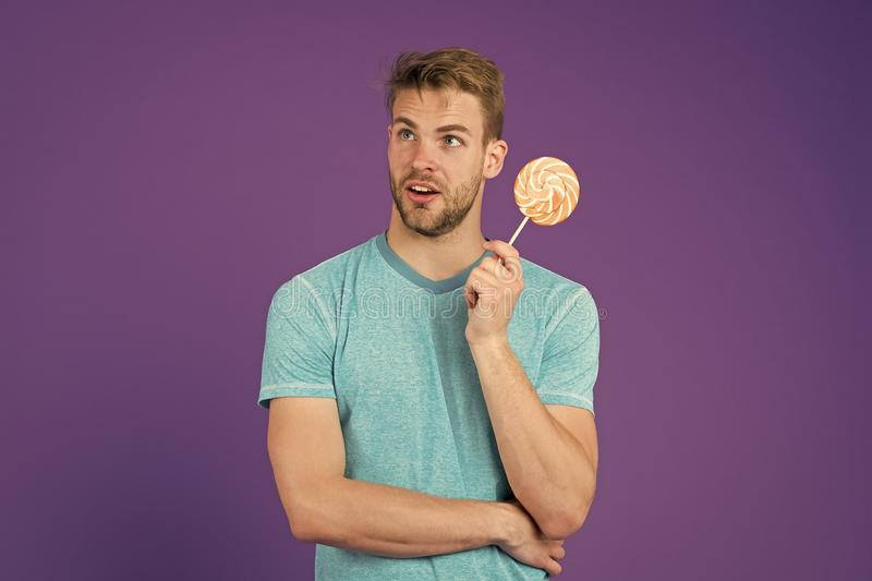 Cheat meal concept. Sugar harmful for health. Guy hold lollipop candy violet background. Man handsome macho eat big stock images