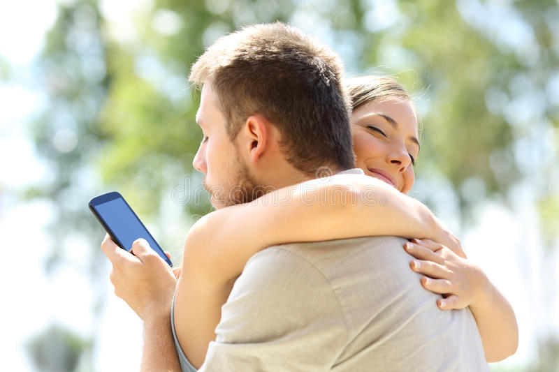 Cheater hugging his innocent girlfriend. Cheater texting with his other lover on phone and hugging his innocent girlfriend royalty free stock images