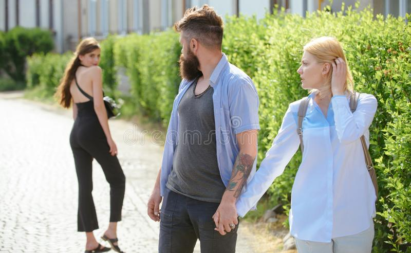He is a cheater. Man cheating his wife or girlfriend. Love triangle and threesome. Bearded man looking at other girl. He is a cheater. Man cheating his wife or royalty free stock photography