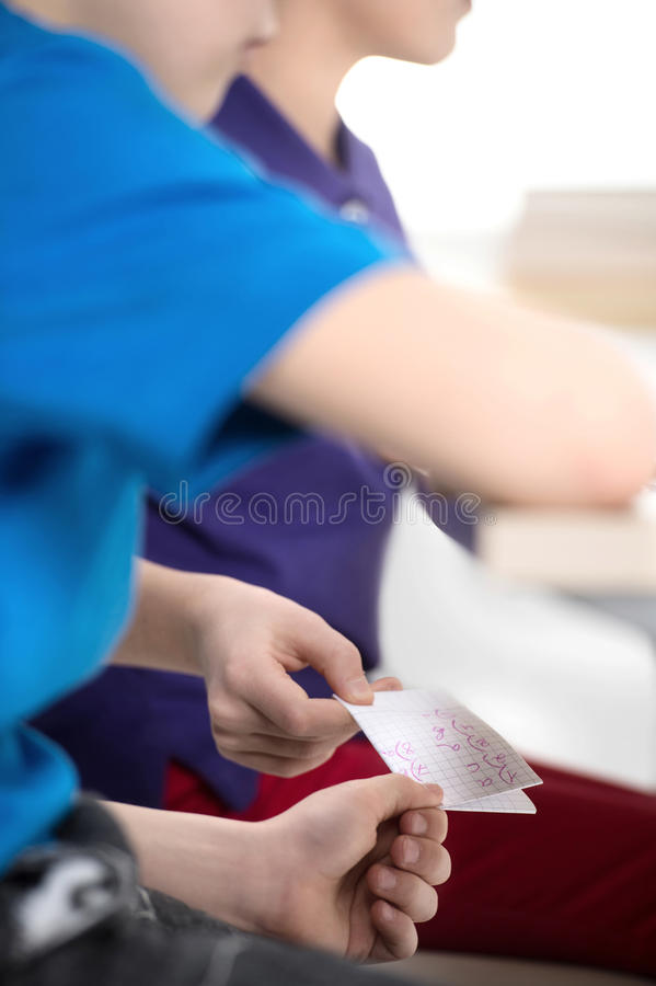 Cheating at the exam. Close up of pupils passing the paper with royalty free stock photo