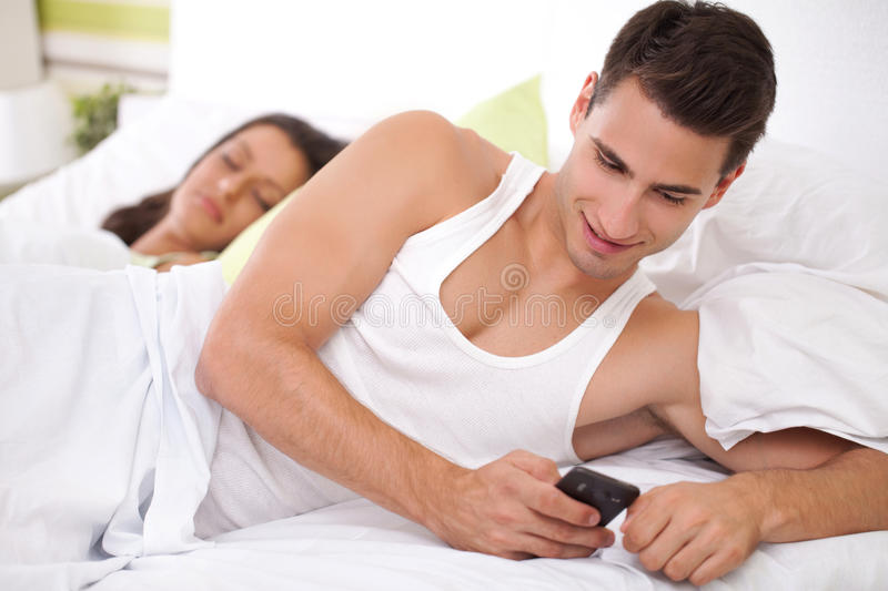 Cheating his wife. Young men chatting with his mistress while his wife sleeps