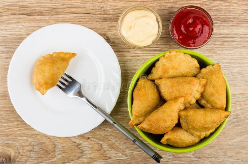Cheburek a ficelé sur la fourchette dans le plat, le ketchup, la mayonnaise et la cuvette image libre de droits