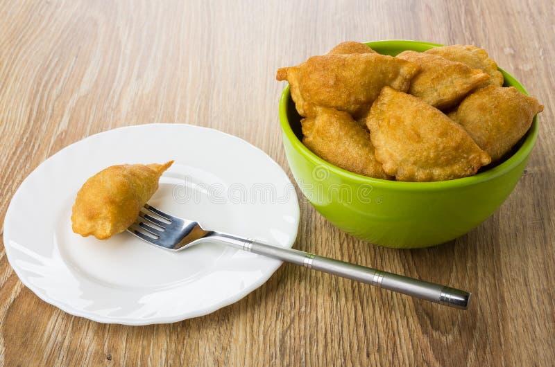 Cheburek a ficelé sur la fourchette et a fait frire des chebureks dans la cuvette verte images stock