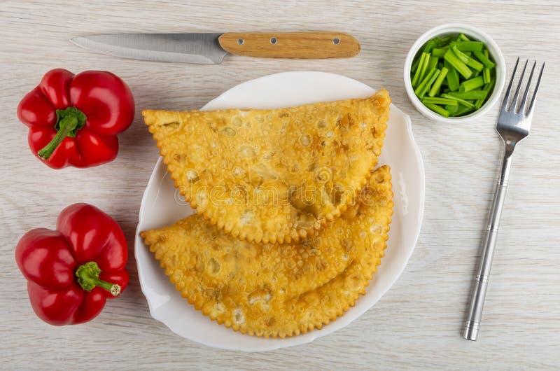 Cheburek frito en el plato, pimientas rojas, cuchillo, cuenco con la cebolleta tajada, bifurcación en la tabla Visión superior fotografía de archivo libre de regalías