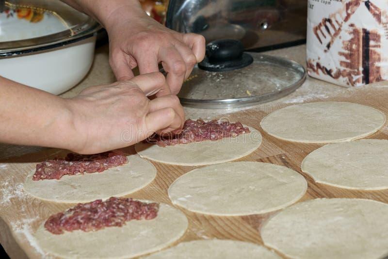 Chebureki Cuisinier à la maison Le seul morceau rond de pâte a replié le remplissage dans une forme en croissant Plat national de photo stock