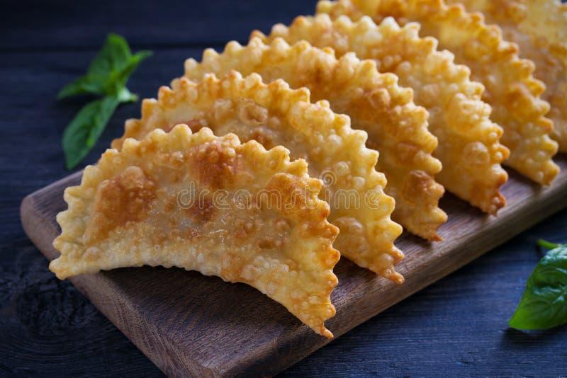 Chebureki - torte fritte con carne e le cipolle, servite sul bordo di legno alimento della Friggere-pasta immagini stock