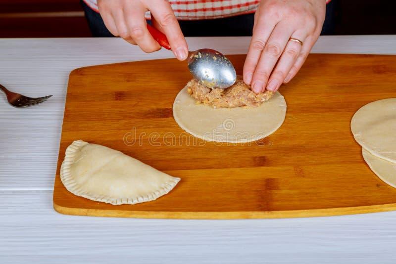 Chebureks Cuoco a casa Cheburek non arrostito con farina su un bordo di legno Il singolo pezzo rotondo di pasta ha ripiegato il m immagini stock