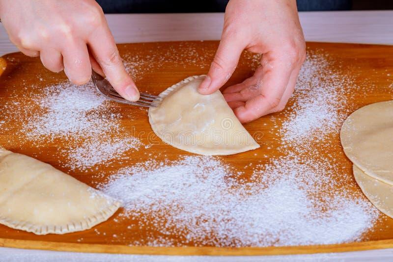 Chebureks Cuoco a casa Cheburek non arrostito con farina su un bordo di legno Il singolo pezzo rotondo di pasta ha ripiegato il m fotografie stock