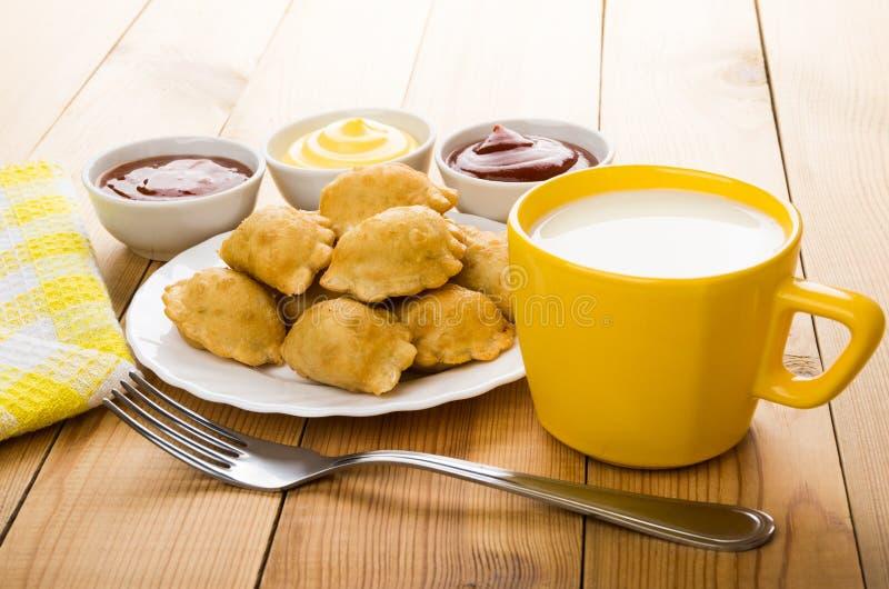 Chebureks dans le plat, différentes sauces dans la cuvette, lait de tasse images libres de droits