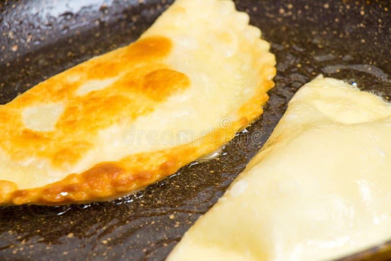 Chebureks are roasted on a hot skillet ruddy crispy tasty royalty free stock photos