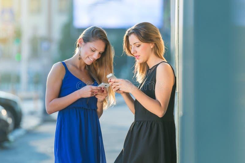 cheching他们的电话的女孩,当在度假在一个城市的在mo时 免版税库存照片
