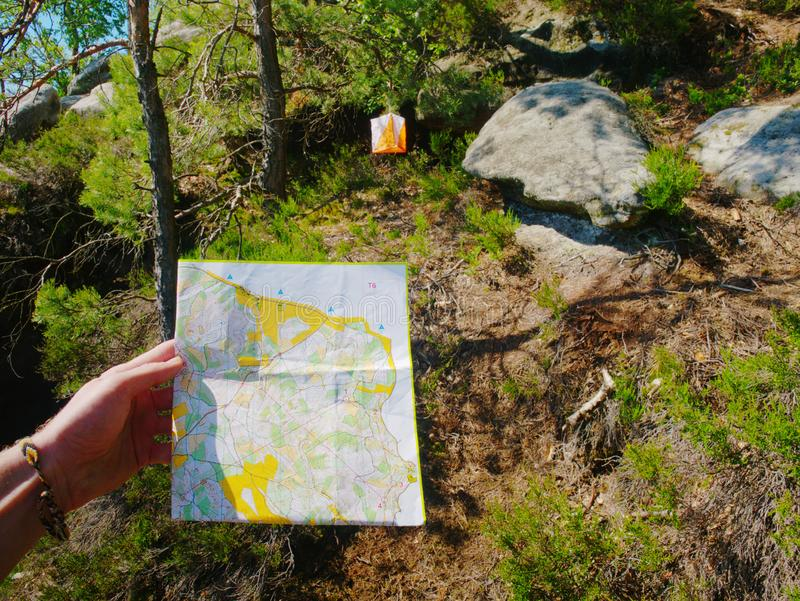 Check the map within orienteering run.  Sportsman running. In difficult rocky terrain, athlete, azimut, azimuth, chart, charts, checkpoint, compass, concept stock image