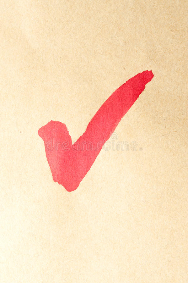 Check mark. Symbol written on brown paper royalty free stock photos