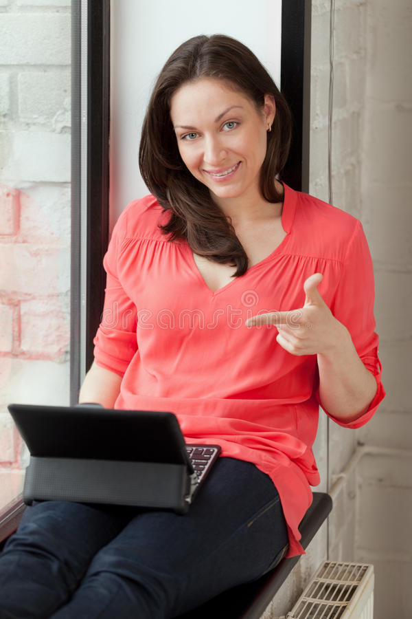Check my website. Girl on windowsill proposes to check her site royalty free stock photo