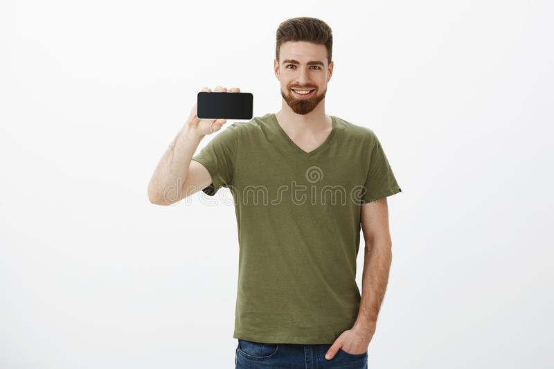 Check out this awesome display. Portrait of confident handsome bearded male coworker holding smartphone horizontal and royalty free stock photo